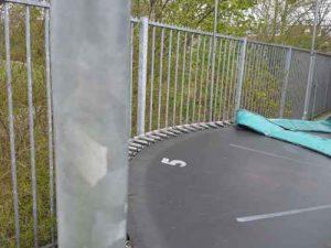 foto Speelplan: trampoline (geen activity toy) naast puntig hek